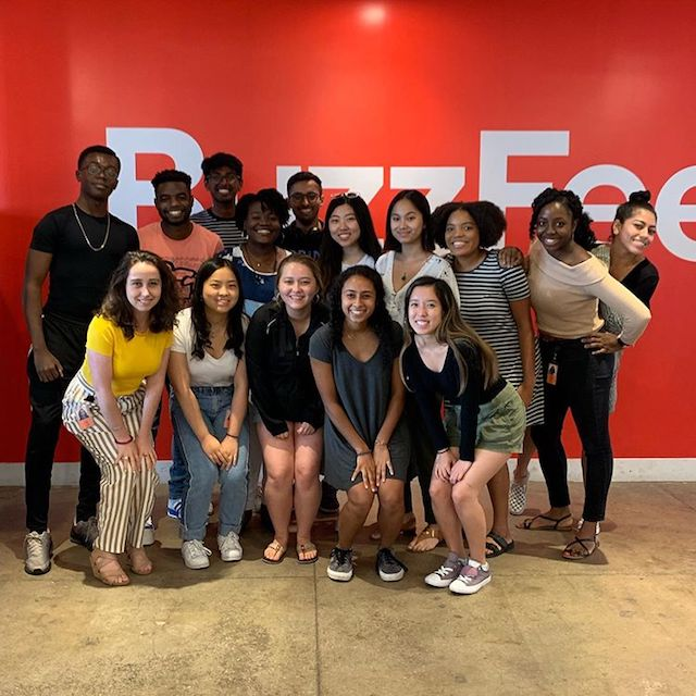Interns posing in front of the BuzzFeed logo.
